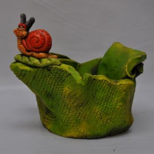 Macetero co hojas verdes y caracol